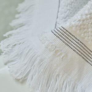 Nærbillede af logo på badehåndklæde med grå stribe